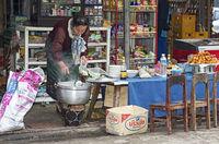 Einheimische Frau schöpft Suppe in eine Tüte an einem kleiner Verkaufsstand, Luang Prabang, Laos
