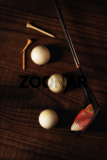 A antique fairway wood with three golf ball and tees on a rustic wood surface.