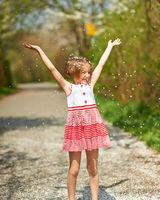 Kind im Frühling wirft Blütenblätter