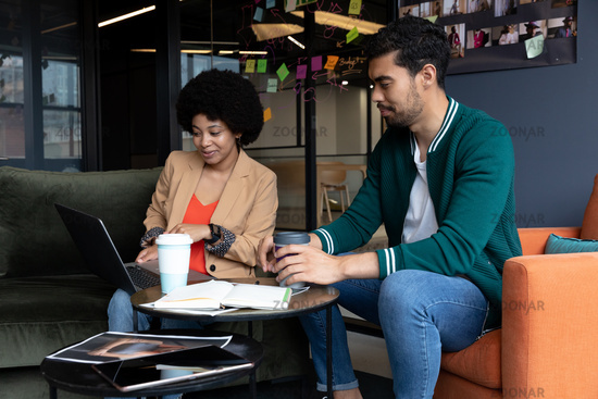 Diverse businessman and businesswoman using laptop having coffee on their break in office