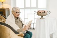 Elegant Senior Woman In Woolen Sweater Is Reading Something On Her Tablet And Smiling