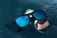 Two fashionable sunglasses on a blue background.