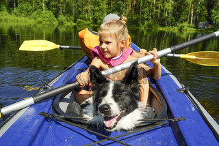 A girl with a dog sitting in a kayak on the lake.