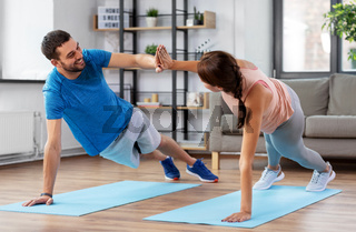 happy couple make high five in side plank at home