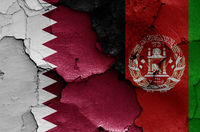 flags of Qatar and Afghanistan painted on cracked wall