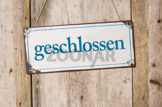 Old metal sign in front of a rustic wooden wall - Closed - geschlossen German
