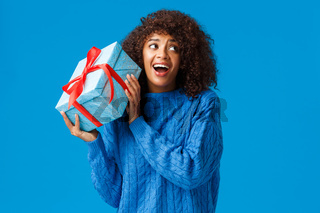 Expectations, holidays and winter concept. Excited cheerful african-american woman shaking box with gift, want unwrap present see what inside standing curious and amused, smiling dreamy