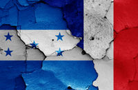 flags of Honduras and France painted on cracked wall