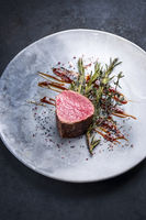 Barbecue dry aged beef fillet medallion steak natural with fried herbs and spice as closeup on a modern design plate with copy space