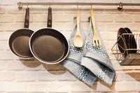 Utensils and pans hanging on railing above counter