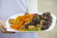 Hands hold a plate of grilled vegetables and mushrooms.