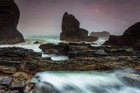 Raging waters over and around jagged craggy coastal rocks