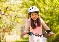 Girl rides on the bike with her toys in the basket
