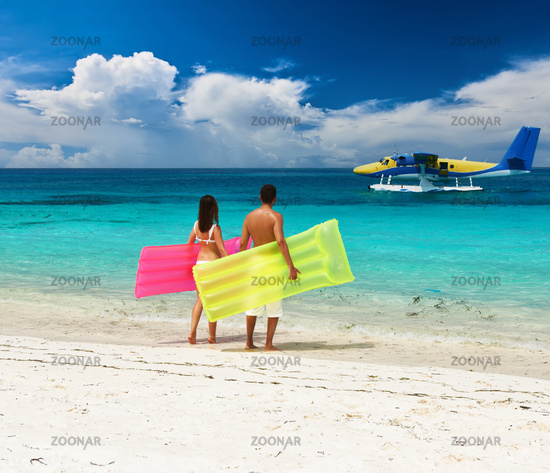 Couple with inflatable rafts looking at seaplane on beach
