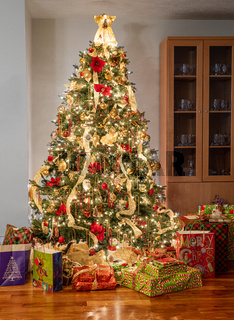 Colorful christmas tree surrounded by wrapped presents and gifts