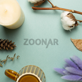 Winter concept. Candle, mug cup, dry plant on green background. top view, copy space