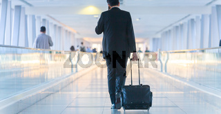 Businessman walking and wheeling a trolley suitcase at the lobby, talking on a mobile phone. Business travel concept.