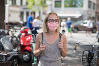 Portrait of casual yound woman walking on the street wearing protective mask as protection against covid-19 virus. Incidental people on the background