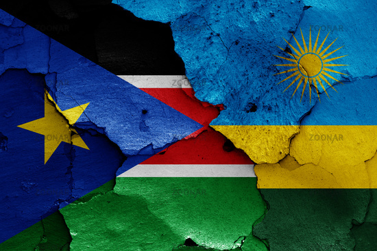 flags of South Sudan and Rwanda painted on cracked wall