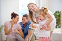 Familie mit Kuchen zu Hause im Wohnzimmer
