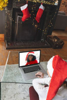 Rear view of woman in santa hat having a videocall with another woman in santa hat smiling on laptop