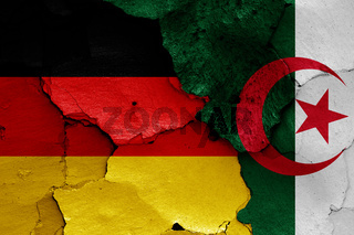 flags of Germany and Algeria painted on cracked wall