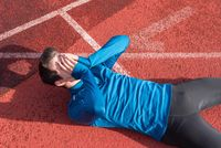 Athlete young man tired, lying on running track.