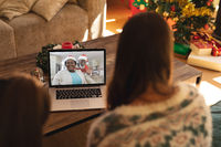 Rear view of woman and son having a videocall with santa claus and senior woman in santa hat on lapt