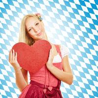 Frau in Dirndl hält rotes Herz