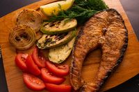 Tasty grilled fish and ingredients for dish on table