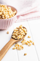 Puffed wheat covered with honey in wooden spoon.
