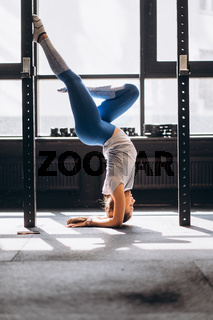 Portrait of attractive young woman doing yoga or pilates exercise