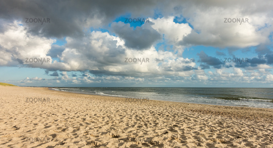 Beach sand with blue sky and dramatic clouds at coastline waterfront in soft evening sunset light. Hvidbjerg Strand, Blavand, North Sea, Denmark.