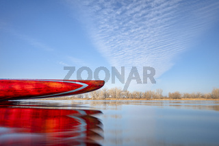 bow of stand up paddleboard on a calm lake,