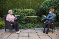 Seniorin und Tochter mit Mundschutz messen Sicherheitsabstand im Garten