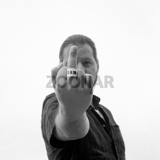 Worker unhappy with his dollar income showing his middle finger. Artistic analog film photography