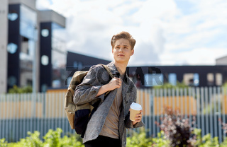 young man with backpack drinking coffee in city