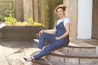 Pregnant Woman In Blue Jumpsuit Sitting On Steps Outdoor