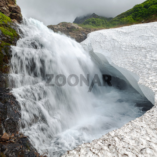 Beautiful view of cascade waterfall falling into glacier in rocky mountain