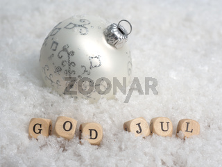Small wooden blocks with the Scandinavian inscription Merry Christmas in the snow