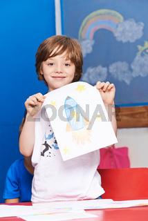 Kind zeigt stolz Rakete auf Blatt Papier