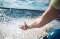 A woman's hand touches the spray on a fast moving boat on the waves of a lake or sea