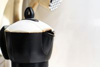 detail of the spout of the black coffee pot with the white lid in a domestic kitchen.Making coffee. Morning routine