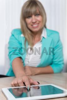 Frau zeigt mit Finger auf ein Tablet