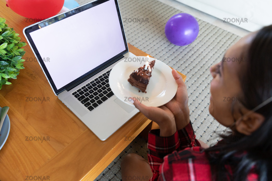 Mixed race woman holding birthday cake using laptop for video chat