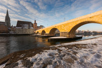 The famous Stone Bridge in the bavarian town Regensburg on sunny winter morning with snow