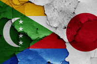 flags of Comoros and Japan painted on cracked wall