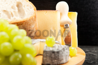 Cheese plate with wine grapes and white bread