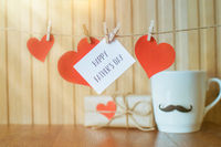 Fathers day message with paper hearts hanging with clothespins over wooden board