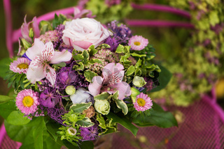Flower bouquet with flower wreath on a garden table